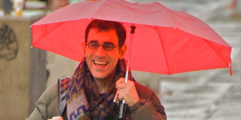 hombre feliz con sombrilla