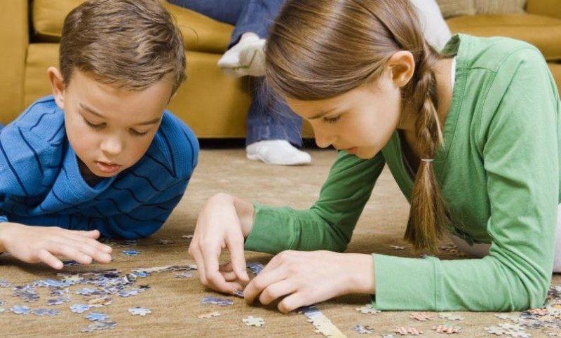 niños armando rompecabezas en casa